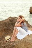 Europea linda niña sosteniendo una concha marina en el mar. — Foto de Stock