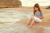 Beautiful girl with long hair and healthy skin on the sea shore and wets feet in water. — Stock Photo