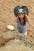 Emotional young girl in a pirate hat is angry and looking for treasure — Stock Photo