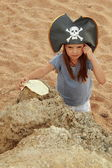 Cute young girl in a pirate hat with a pirate map in hand — Stock Photo