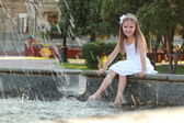 Joyful young girl with beautiful hair wets feet in a fountain on a hot summer day — Stock Photo