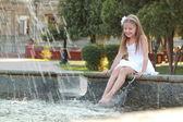 Cheerful cute little girl in white dress sitting near the fountain — Stock Photo
