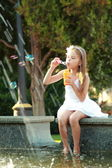 Smiling happy little girl in white dress enjoying cool water in a fountain — Stockfoto