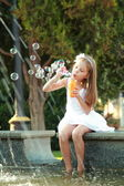 Cute smiling young girl in a beautiful white dress flounder feet in the fountain — Stock fotografie
