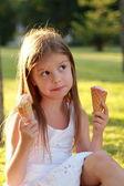 Portrait d'une fillette pensive avec un sourire choisit la crème glacée sur une chaude journée d'été — Photo