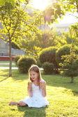 Encantadora chica joven con una dulce sonrisa en vestido blanco sentada sobre la hierba y comiendo un helado — Foto de Stock