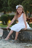 Smiling happy little girl in white dress enjoying cool water in a fountain — Stock Photo