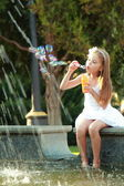 European girl in a white dress blowing soap bubbles in summer park. — Stock Photo