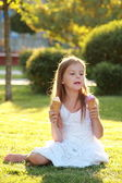 Contented smiling little girl is holding two ice creams — Foto de Stock