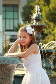 Beautiful little girl in a white dress near the fountain in the hot summer day outdoors — Stock Photo