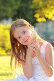 Heureuse mignonne petite fille en vêtements décontractés manger la crème glacée sur un fond de nature en été — Photo