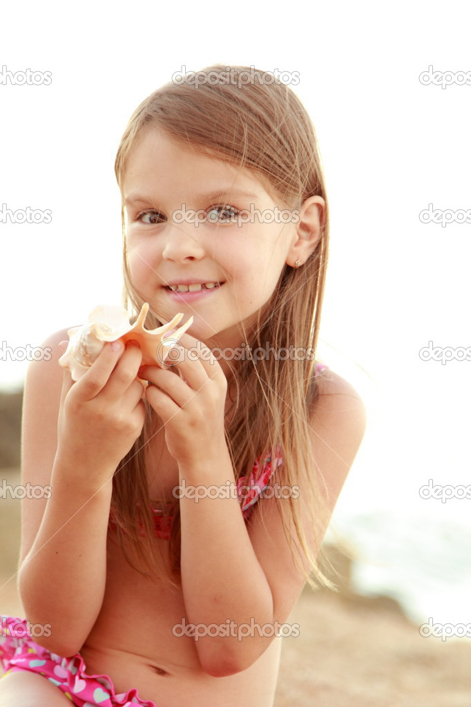 Cute smiling little girl in a bathing suit sits on a background of sea sand stock photo - Pics of small little girls ...