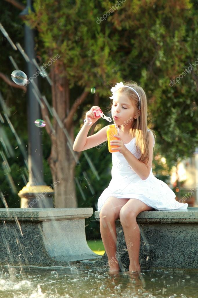 Little Girl Playing And Having Fun Enjoying The Spray Of