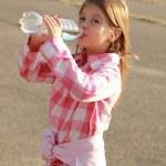 Cute little girl drinks water — Stock Photo