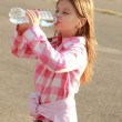 Cute little girl drinks water — Stock Photo