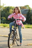 Cheerful little girl riding a bicycle — Stock Photo