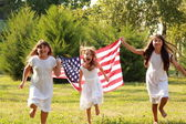 Schoolchildren with an American flag — Stock Photo