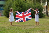 Little girls carry the flag of the UK — Stock Photo