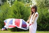 Cute girl holding a big Britain flag — Stock Photo