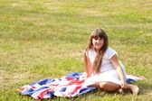 Girl holding a big flag of Great Britain — Stock Photo