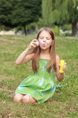 Beautiful girl in played with soap bubbles — Foto Stock