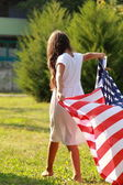 Girl holding a large American flag — Stock Photo