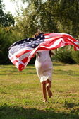 Girl holding a large American flag — Foto de Stock