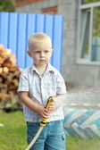 Little watering the lawn — Stock Photo