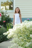 Little girl in the yard on a summer day — Stockfoto