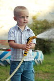 Little blond boy watering the lawn — Stock Photo