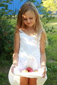 Little girl sitting on grass and holding apples — Stock Photo