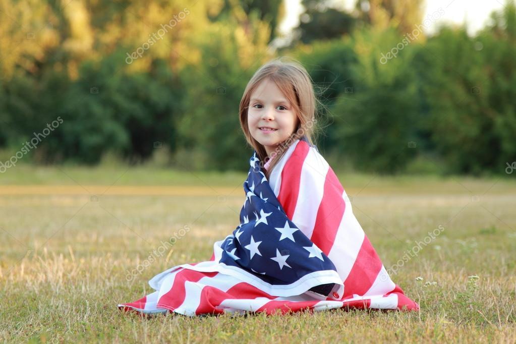 可爱开朗的小女孩躺在球场上的美国国旗– 图库图片