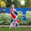 Cheerful beautiful young girl running with the flag of the UK in the summer garden — Stock Photo #30070549
