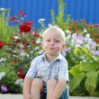 Smiling little blond boy is playing on the background of beautiful flowers outdoors — Foto de Stock