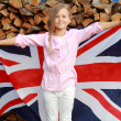 European smiling little girl holding a big UK flag outdoors — Stock Photo