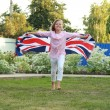 Cheerful beautiful young girl running with the flag of the UK — Stock Photo
