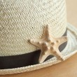 Starfish and summer hat on the old wooden background — Stock Photo