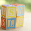 Word sale of children's colored blocks for learning alphabet — Stock Photo #30073775