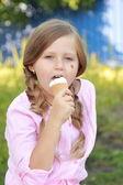 Lovely girl eating ice cream outdoor — Stock fotografie