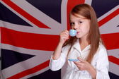 Little girl on the background of the flag of UK — Stock Photo