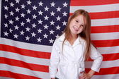 Girl against the background of the American flag — Stock Photo