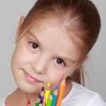 Little schoolgirl holds a pencil — Stock Photo