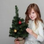 flicka som håller en liten julgran — Stockfoto
