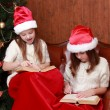 Girls wearing Santa hats holding books — Stock Photo