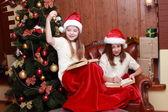 Meisjes dragen santa hoeden houden boeken — Stockfoto