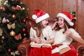 Girls wearing Santa hats holding books — Stock Photo