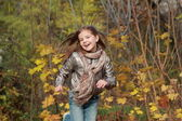 Kid running in autumn forest — Stock Photo