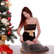 Woman playing with cat near Christmas tree — Stock Photo