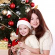 Mother and child girl in Santa hats — Stock Photo