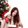 Mother and daughter holding cat over Christmas tree — Stock Photo #36138121